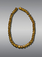Bronze Age Hattian gold necklace from Grave L,  possibly a Bronze Age Royal grave (2500 BC to 2250 BC) - Alacahoyuk - Museum of Anatolian Civilisations, Ankara, Turkey. Against a gray background .<br /> <br /> If you prefer to buy from our ALAMY PHOTO LIBRARY  Collection visit : https://www.alamy.com/portfolio/paul-williams-funkystock/royal-tombs-alaca-hoyuk-bronze-age.html (TIP refine search by adding background colour in the LOWER search box)<br /> <br /> Visit our ANCIENT WORLD PHOTO COLLECTIONS for more photos to download or buy as wall art prints https://funkystock.photoshelter.com/gallery-collection/Ancient-World-Art-Antiquities-Historic-Sites-Pictures-Images-of/C00006u26yqSkDOM