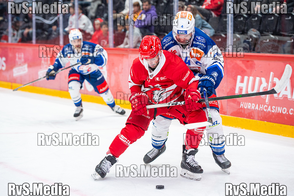 LAUSANNE, SWITZERLAND - OCTOBER 01: Jason Fuchs #14 of Lausanne HC battles for the puck with Patrick Geering #4 of ZSC Lions during the Swiss National League game between Lausanne HC and ZSC Lions at Vaudoise Arena on October 1, 2021 in Lausanne, Switzerland. (Photo by Monika Majer/RvS.Media)
