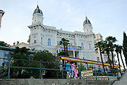 Two children (9 years old, 5 years old) wearing French berets, sitting on railing with Admiral Casino building in background. Opatija, Croatia