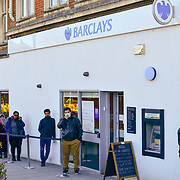 Coronavirus threat - People queue outside Barclays Bank only allow one at a time to entry bank, on 23 March in Walthamstow, London, UK.