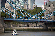 A met police officer in a police launch boat picks an item from the waters of the River Thames beneath the Victorian-era Tower Bridge with the Norman Tower of London in the capital's financial district (aka The Square Mile) behind, on 5th October, 2017, in London, England. The Gabriel Franks is a Fast Response Targa 31 boat of the Metropolitan Police Marine Policing Unit, named after the first British marine police officer to be killed in the line of duty.