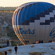 Huge hot air balloon fly down the rock in the morning in Cappadocia, Turkey
