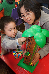 United States, Washington, Bellevue, KidsQuest Children's Museum, mother and boy with toy at family math night with Explorations in Math