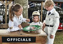 © licensed to London News Pictures. 12/09/2015<br /> Goodwood Revival Weekend, Goodwood, West Sussex. UK.<br /> The Goodwood Revival is the world's largest historic motor racing event. Competitors and enthusiasts dress in period fashions recreating the glorious days of the race circuit.<br /> Pictured Three young Austin J40 peddle car drivers take a break in-between races to play with a vintage toy.<br /> <br /> Photo credit : Ian Whittaker/LNP