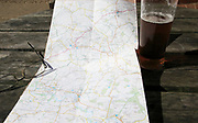 Ordnance Survey Explorer map opened on table with spectacles and pint glass of beer, Suffolk, England, UK
