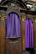 Purple Catholic confessional curtains in St Vitas' Cathedral in Prague Castle, on 18th March, 2018, in Prague, the Czech Republic. The Metropolitan Cathedral of Saints Vitus, Wenceslaus and Adalbert is a Roman Catholic metropolitan cathedral in Prague, the seat of the Archbishop of Prague. Until 1997, the cathedral was dedicated only to Saint Vitus, and is still commonly named only as St. Vitus Cathedral. This cathedral is a prominent example of Gothic architecture and is the largest and most important church in the country. It is located within Hradcany-Prazsky Hrad (Prague Castle) in the Czech capital.