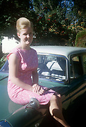 Young European lady sits on the bonnet of a car in Blantyre, Malawi in the mid-1960s. Perched on the front of the vehicle, the woman wears a pink dress with a pink paisley pattern, popular in the sixties. Smiling to the viewer, she sits upright with hands across her lap, having removed her sun galasses which she holds folded up in her hand. There is a lush tropical garden behind belonging to an unknown owner in the African Malawi town.
