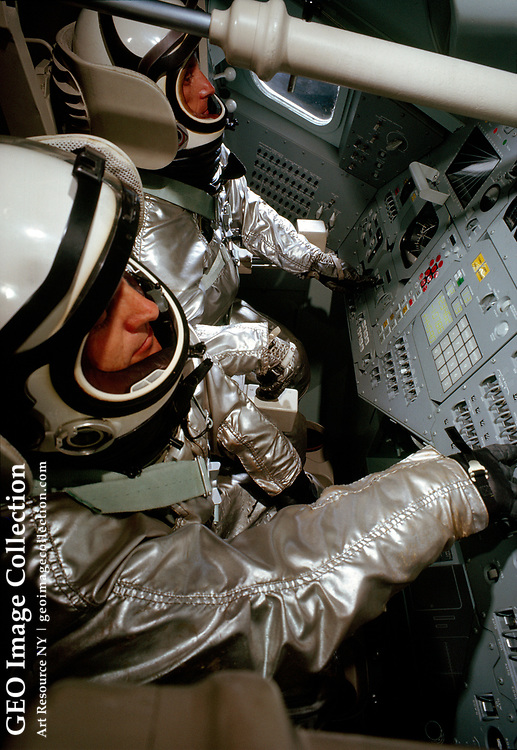 Two pressure-suited test subjects sit in the seats of a mock-up Apollo command module during tests.