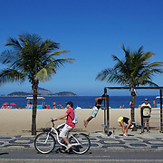 A jogger and cyclist pass a fitness workstation on the edge of Ipanema Beach, Rio de Janeiro, Brazil. 4th July 2010. Photo Tim Clayton..The beaches of Rio de Janeiro, provide the ultimate playground for locals and tourists alike. Beach activity is in abundance as beach volley ball, football and a hybrid of the two, foot volley, are played day and night along the length and breadth of Rio's beaches. .Volleyball nets and football posts stretch along the cities coastline and are a hive of activity particularly at it's most famous beaches Copacabana and Ipanema. .The warm waters of the Atlantic Ocean provide the ideal conditions for a variety of water sports. Walkways along the edge of the beaches along with exercise stations and cycleways encourage sporting activity, even an outdoor gym is available at the Parque Do Arpoador overlooking the ocean. .On Sunday's the main roads along the beaches of Copacabana, Leblon and Ipanema are closed to traffic bringing out thousands of people of all ages to walk, run, jog, ride, skateboard and cycle more than 10 km of beachside roadway. .This sports mad city is about to become a worldwide sporting focus as they play host to the world's biggest sporting events with Brazil hosting the next Fifa World Cup in 2014 and Rio de Janeiro hosting the Olympic Games in 2016...