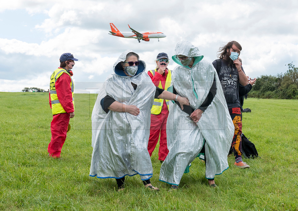 © Licensed to London News Pictures;29/08/2020; Bristol Airport, Lulsgate Bottom, UK. A plane comes into land as protesters gather for a Common Ground with Extinction Rebellion protest at Bristol Airport against plans to expand the airport and against the airport's decision to appeal against a refusal by North Somerset Council over the expansion plans. This is on the second day of a bank holiday weekend of protest across the UK by Extinction Rebellion. XR are protesting in Bristol and other cities in the UK against climate change, leading up to a protest in London starting on 01 September. XR say that despite clear scientific evidence of the deadly climate and ecological emergency, the UK government are refusing to take the urgent action needed to avoid mass extinction. XR say we need politicians to support the Climate and Ecological Emergency Bill. During the coronavirus covid-19 pandemic, climate change is being forgotten but it is still an emergency that is happening, the elephant in the room. Photo credit: Simon Chapman/LNP.