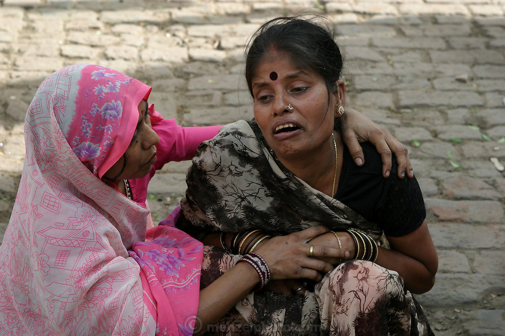Durga Tiwari, 35, is comforted by a family member as her mother, Savitridevi Mishra, is taken to the cremation grounds of Jalasi Ghat. This after the body has been washed, draped in a red and yellow shroud and marigold garlands and photographed for a family remembrance.