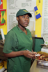 Woman working in Caribbean café writing down food order,