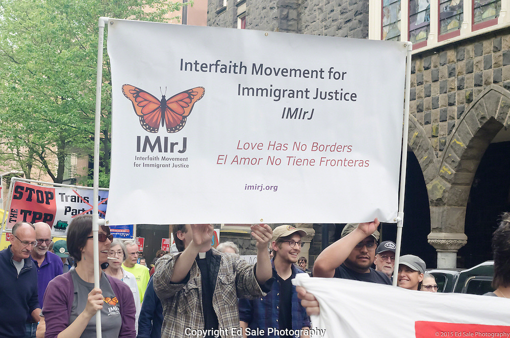 Demonstrators in 2015 May Day rally and march in Portland, Oregon hold large banner saying Interfaith Movement for Immigrant Justice
