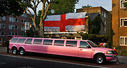 A pink stretch limousine parked outside a George flag displayed in  the entrance to the Victory pub on the 2nd June 2006 in Camden, London, United Kingdom.  England went out of the World Cup on penalties in the quarter-final against Portugal. .
