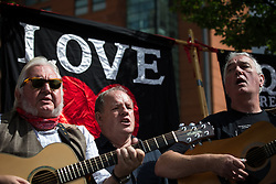 """© Licensed to London News Pictures . 16/08/2015 . Manchester , UK . Actor JOHN HENSHAW sings at a memorial to the """" Peterloo Massacre """" at the site of St Peter's Field , where fifteen people were killed during a cavalry charge on a democracy protest , 196 years ago (16th August 1819) . Photo credit : Joel Goodman/LNP"""