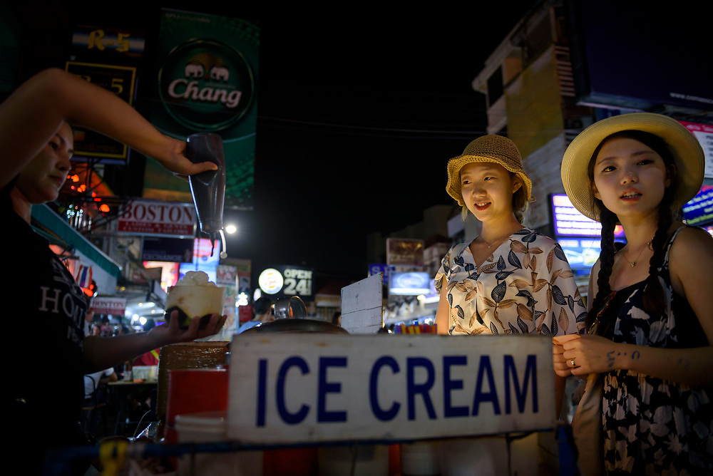 Two tourists from South Korea order coconut ice cream served in a coconut shell on Khao San Road in Bangkok, Thailand. The street is a legendary backpacker hangout, lines with shops, bars, restaurants, and food vendors. (June 2017)