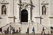 Pedestrians pass by Loreto Church in Chiado district in Lisbon.