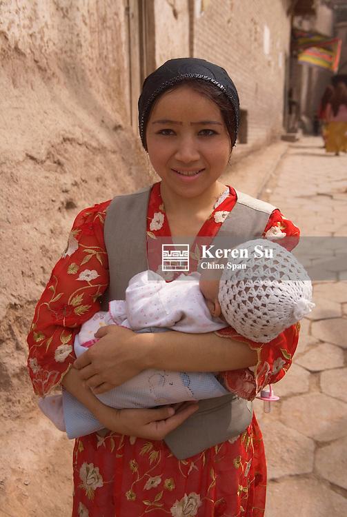 Uighur woman carrying baby in traditional alley, Kashgar, Xinjiang, Silk Road, China