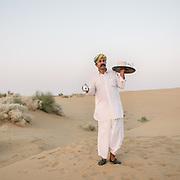 A waiter bringing tea chai. Sunset camel ride in the dunes of the Thar desert.