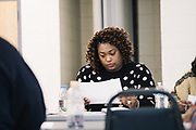 """SELMA, AL – DECEMBER 19, 2019: Keshee Dozier-Smith, 34, looks over documents at a YMCA Board of Directors meeting. Dozier-Smith took her seat on the Selma-Dallas County YMCA Board of Directors in September, 2019, and views her involvement there as an opportunity to encourage overall fitness and wellness within the community, and within the Rural Health Medical Program network. """"It's really part of our broader mission at Rural Health Medical Program – helping our patients connect with the community through health, fitness and wellness, and to bring people from different walks of life together.""""<br /> <br /> Since joining Rural Health Medical Program as Chief Executive Officer in March 2016, Dozier-Smith has effectively moderned the 35-year-old floundering business – opening three new clinics, streamlining processes and reaching out to local companies to offer healthcare services for employees. In the wake of rising hospital closures that leave Alabama's poorest citizens disproportionately cut off from access to medical care, Dozier-Smith represents a renewed effort to bridge the rural gap by offering a quality, affordable healthcare option."""