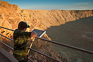 Young boy tourist looking out over Meteor Crater, also known as Barrenger Crater, near Winslow, Arizona