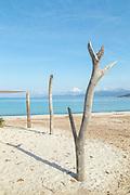 Piles on beach and sea under blue sky, Beach of Porticcio, Gulf of Ajaccio, Corsica, France
