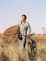 Man walking with a bicycle in a grassy area,  carrying a surfboard
