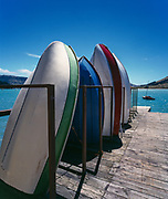 Licensing - Open Edition Prints Dinghies standing up on dock with sailboat in distance in Sumner near Christchurch on the South Island of New Zealand