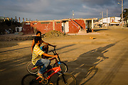 2016/10/09 – Jama, Ecuador: Children ride bikes on a street of Jama, Ecuador in from of one of the many collapsed buildings, 9th October 2016. By Government sources, more than 50% of Jama was destroyed by the earthquake. The earthquake reached the magnitude of 7.8 on the Richter scale hit the Ecuadorian coast, where more than a million and half of people live, circa 10% of the total population of the country. (Eduardo Leal)
