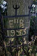 Ironwork celebrating Queen Elizabeth's coronation in 1953, around an oak tree at a remote lane near Irstead in rural Norfolk.