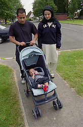 Father pushing young son in pushchair while mother walks alongside,
