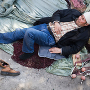 An Afghan man rests on fishing nets in Molyvos port hours after his boat has been rescued by the Greek Coast Guard. Everyday hundreds of refugees, mainly from Syria and Afghanistan, are crossing in small overcrowded inflatable boats the 6 mile channel from the Turkish coast to the island of Lesbos in Greece.