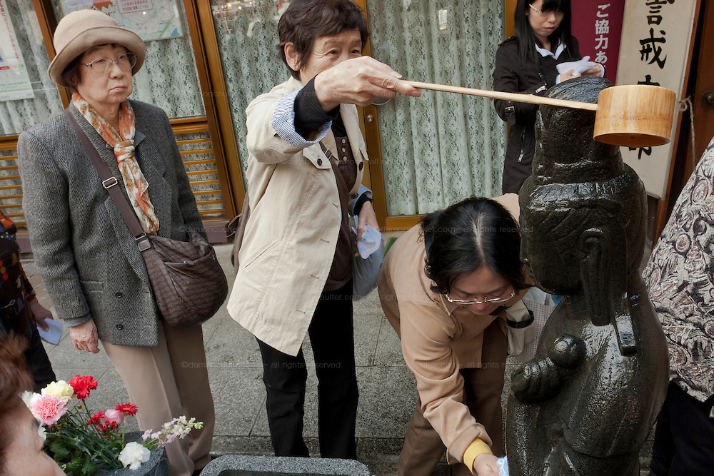 Older Japanese women pour water onto the Arai Kannon statue at Tognaji Temple in  Sugamo, Tokyo, Japan Wednesday, April 14th 2010. Sugamo is affectionately known as the old lady Harajuku, in reference to the Mecca for youth fashions in the South of Tokyo, and is a popular place for Tokyo's increasingly aged population. The Arai Kannon statue is a famous religious icon at Togan-ji temple in the heart of Sugamo, where people go to rub the statue with a white cloth in the hopes of curing sickness and ensuring a long, healthy life.