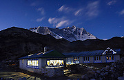 The dining hall of a teahouse, or trekking lodge, glows at twilight in Chhukung (a side trip off the Everest Base Camp trek), Khumbu region, Sagarmatha National Park, Himalaya Mountains, Nepal. The summits of Nuptse and Lhotse are visible in the distance.