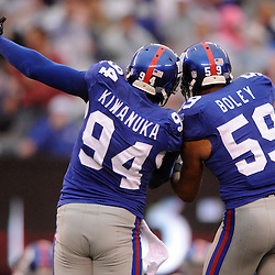 New York Giants defensive end Mathias Kiwanuka (94) and linebacker Michael Boley (59) celebrate Kiwanuka's sack and forced fumble during second half NFL action in the New York Giants' 31-18 victory over the Carolina Panthers at New Meadowlands Stadium in East Rutherford, New Jersey.