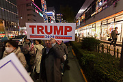 "A Japanese man, holds a sign reading Trump- 2020 as several hundred people, taking part in a ""March For Trump"" rally  in support of the out-going United States President, Donald Trump. Tokyo, Japan. Wednesday January 6th 2021. The rally of mostly Japanese people took place as part of a similar rally by Trump-supporters in Washington DC as the results of the 2020 US Presidential election were confirmed."