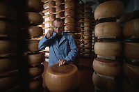 November 1989, Parma, Italy --- Man Smelling a Sample of Parmesean Cheese --- Image by © Owen Franken/CORBIS