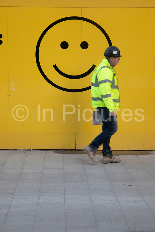 Workman in a high viz jacket walks past a smiley face motif on a yellow wall in London, England, United Kingdom. A smiley, sometimes called a happy face or smiley face, is a stylised representation of a smiling humanoid face that is a part of popular culture worldwide. The classic form designed by Harvey Ball in 1963 comprises a yellow circle with two black dots representing eyes and a black arc representing the mouth.