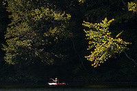 Woman kayaking in a beautiful, pristine Vermont lake during summer.  Greenwood Lake, Vermont