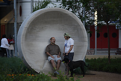 Stock photo of a couple with their dog using the listening vessels in the gardens of Discovery Green