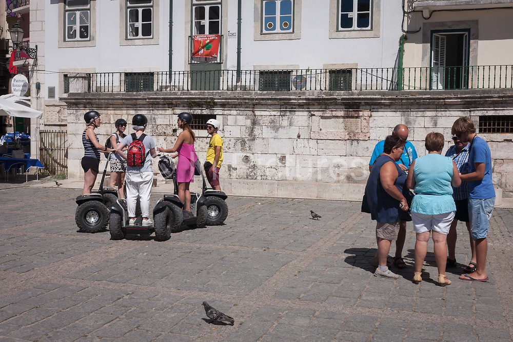 Joined by two pigeons to separate them, a group of Segway tourists stop to hear their guide describe the medieval and Moorish Alfama districts history, ironically next to a crowd of like-minded pedestrians, on 11th July 2016, in Lisbon, Portugal. Segway tours have become controversial additions to the European city sightseeing scene, already being banned in Barcelona and Prague. But in Portuguese cities like Lisbon and Porto, Segway travellers still share narrow and busy streets and often, pavements, with locals on foot.