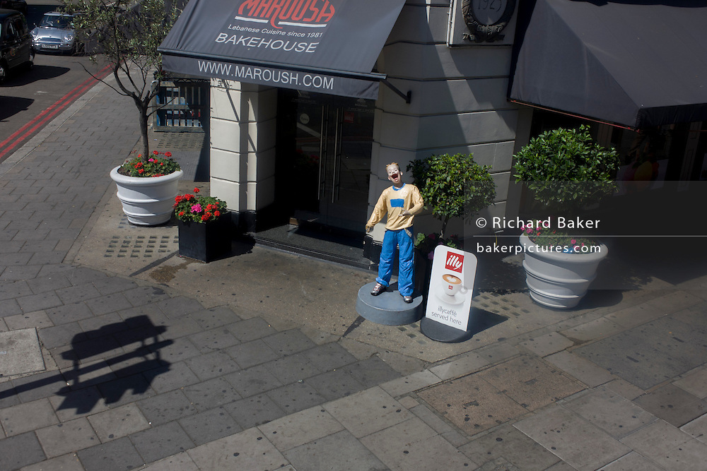 Seen from a London bus, a lone mannequin stands on Edgeware Road promoting the Bakehouse Marousha.