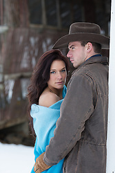 girl in a blanket being held by a hot cowboy