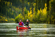 Yukon Territory, Canada, September 2014. Two paddlers navigate their canoe through the autumn landscape of the Yukon River. During this Yukon River canoe trip we paddled part of the Klondike Gold Rush route of 1898. We camped on the banks of the Yukon River in authentic northern wilderness and explored the gold rush relics on the way. Photo by Frits Meyst / MeystPhoto.com