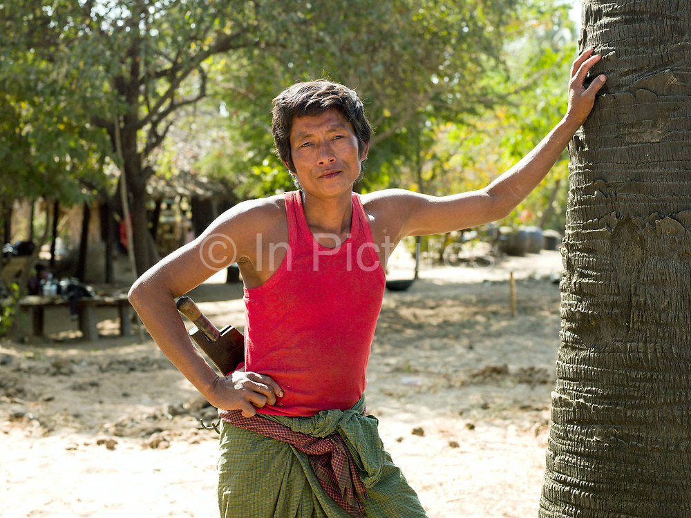 Portrait of a toddy palm farmer, Mandalay region, Myanmar (Burma). The sap of the palm tree is used for for making toddy (an alcoholic drink) and jaggery (palm sugar).