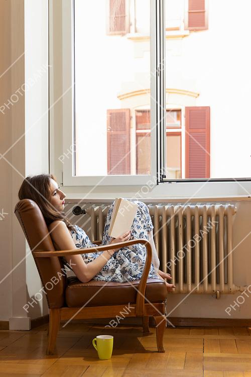 woman sitting in an armchair near a window reading a book