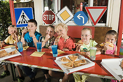 Children eating pizza at driver training area