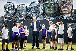 """© Licensed to London News Pictures. 21/07/2021. Stockport, UK.  Children from St Matthews C of E Primary School in Stockport visit the installation and ask questions of musicMagpie CEO STEVE OLIVER . The E7 , a Mount Rushmore-style sculpture also known as """" Mount Recyclemore """" , is unveiled outside the Stockport headquarters of recommerce company musicMagpie , who commissioned the sculpture for the G7 summit in June to much media interest . The sculpture was created out of e-waste in the likeness of the G7 leaders by artist and founder of the Mutoid Waste Company, Joe Rush , and will serve as an educational attraction during events hosted this summer , in collaboration with Totally Stockport and Stockport Council . Photo credit: Joel Goodman/LNP"""