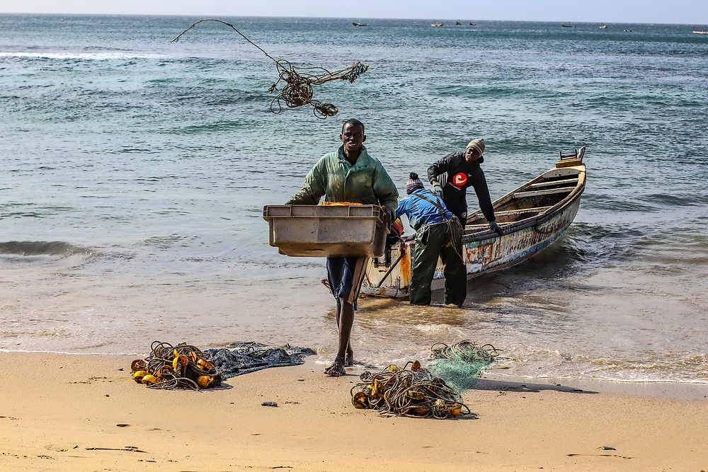Fishermen unload the days catch and bring supplies ashore from a pirogue, in Senegal, West Africa. Credit: Jack Rodine/UoG/PathosImages