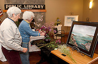 Judy Nelson and Evelyn Millar work together to assemble their floral interpretation of Sunrise painted by Jaylene Bengston in preparation for Opechee Garden Club's Art 'n Bloom at Gilford Public Library beginning Thursday at 10 am.  (Karen Bobotas/for the Laconia Daily Sun)